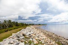 Weergeven van een vuilmuur van keien langs de kust van de Atlantische Oceaan, Guyana op de achtergrond van blauwe hemel stock foto