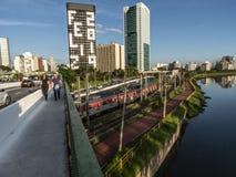 Weergeven van gebouwen, CPTM-trein, verkeer van voertuigen en rivier in Marginale Pinheiros-Rivierweg stock afbeeldingen