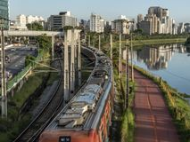 Weergeven van gebouwen, CPTM-trein, verkeer van voertuigen en rivier in Marginale Pinheiros-Rivierweg stock fotografie