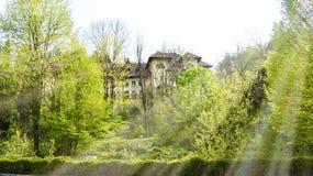 Weergeven van groot verlaten hotel met oude architectuur hiddent in het bos in een zonnige de lentedag stock fotografie