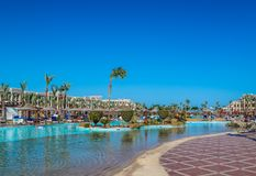 Weergeven van het gebied van de hotel'srecreatie op het strand en de overzeese kust, palmen onder de blauwe hemel van een zonni stock foto