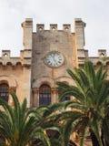 Weergeven van het historische die stadhuis in ciutadellamenorca door palmen en blauwe zonovergoten de zomerhemel wordt omringd royalty-vrije stock fotografie
