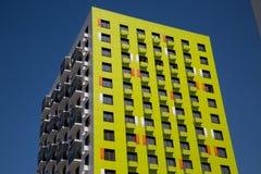 Weergeven van het nieuwe mooie flatgebouw van geelgroene kleur met oranje tussenvoegsels, scharnierende verglaasde balkons stock foto