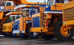 Weergeven van het parkeerterrein van een tentoonstelling van de grote vrachtwagens van de carrière zware stortplaats bij de autom stock foto