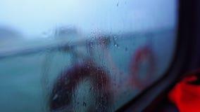 Weergeven van het venster van de passagiersboot, regenachtige dag stock video