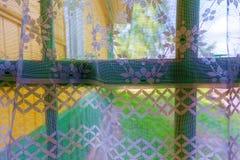 Weergeven van het venster van een buitenhuis door het gordijn royalty-vrije stock afbeelding