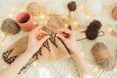 Weergeven van hierboven van de handen die van de vrouw warme beige sweater breien Huis, freelance, met de hand gemaakt stemmingsc stock foto's