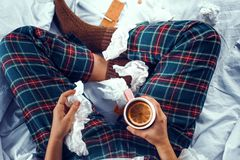 Weergeven van hierboven op zieke vrouw die in bed een kop thee met sinaasappel daarin houden stock foto's