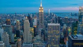 Weergeven van horizon de van de binnenstad van Manhattan, New York, de V.S., bij nacht tijdens schemering stock foto