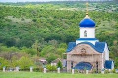 Weergeven van kleine Orthodoxe kerk met blauwe koepels op reparatie in Rusland stock foto's