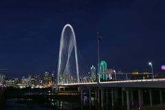 Weergeven van Margaret Hunt Bridge met Dallas Skyline op de achtergrond bij nacht royalty-vrije stock afbeeldingen