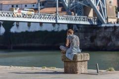 Weergeven van meisjeszitting op steenbank, op de dokken van de stroom in Porto stad, brug als achtergrond stock fotografie