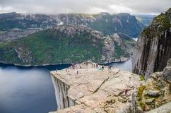 Weergeven van mensen die op Preikestolen-Preekstoelrots lopen van hierboven met een fjord onderaan stock foto's