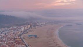 Weergeven van Nazare-panorama met cabines van Kabeltimelapse Mist die uit oceaan bij avond tijdens zonsondergang komen stock video