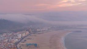Weergeven van Nazare-panorama met cabines van Kabeltimelapse Mist die uit oceaan bij avond tijdens zonsondergang komen stock videobeelden