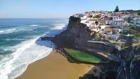 Weergeven van oceaangolven op strand dichtbij het kleine dorp Azenhas do Mar van Portugal stock video