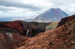 Weergeven van Onderstel Ngauruhoe - zet Noodlot van de Alpiene Kruisende stijging van Tongariro met wolken hierboven en rode krat stock foto's