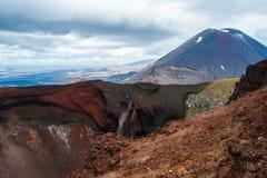 Weergeven van Onderstel Ngauruhoe - zet Noodlot van de Alpiene Kruisende stijging van Tongariro met wolken hierboven en rode krat royalty-vrije stock afbeelding