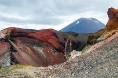Weergeven van Onderstel Ngauruhoe - zet Noodlot van de Alpiene Kruisende stijging van Tongariro met wolken hierboven en rode krat royalty-vrije stock fotografie