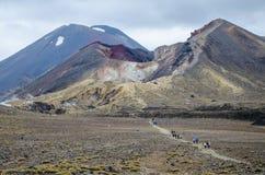 Weergeven van Onderstel Ngauruhoe - zet Noodlot van de Alpiene Kruisende stijging van Tongariro met wolken hierboven en rode krat stock foto