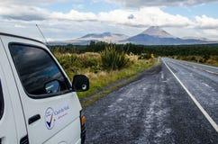 Weergeven van Onderstel Ngauruhoe - zet Noodlot van weg in het Nationale Park van Tongariro met witte autobestelwagen in op de vo royalty-vrije stock foto