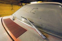 Weergeven van oude retro Amerikaanse auto in garage met stoffige kap vuile voorruit met titelverkoop door vinger en brok stock foto