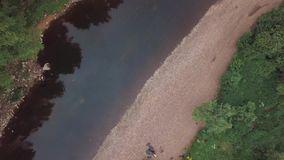 Weergeven van rivier en steenachtige grondrivieroevers dichtbij struiken, gras en bomen, en bedrijf van toeristen die zich op bev stock footage