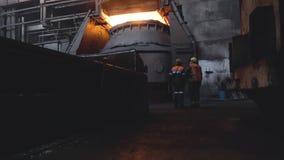 Weergeven van twee arbeiders van terug in eenvormig en helmen op achtergrond van donkere vuile fabriek lengte Twee werknemers con stock video