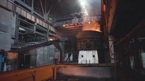 Weergeven van uitsmelting van metaal met gietlepel binnen gieterij lengte Binnenland van vuile metallurgische installatie in dark stock videobeelden
