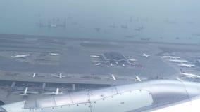 Weergeven van venster vliegend vliegtuig over luchthaven en overzees Vleugelvliegtuig die boven schepen in blauwe oceaan vliegen  stock videobeelden