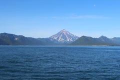 Weergeven van Vilyuchinsky-vulkaan & x28; ook geroepen Vilyuchik& x29; van water De maan is zichtbaar in de hemel royalty-vrije stock afbeeldingen