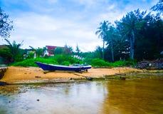 Weergeven van vissersboot op het gele zandige strand met kokosnotenpalmen royalty-vrije stock afbeelding
