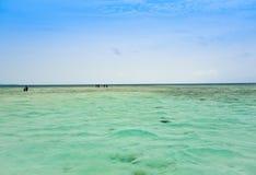 Weergeven van visserstoeristen die op het ondiepe water van kalme oceaan lopen stock fotografie