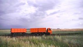 Weergeven van vrachtwagen met hoge capaciteit met lichaam het reizen op landelijke weg door landbouwbedrijfgebieden scène Landsch stock footage