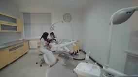 Weergeven van vrouwelijke tanden die behandeling in tandkabinet reinigen stock video