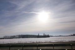 Weergeven van weg van de weiden en de gebieden van het de winterlandschap die met laag van sneeuw worden behandeld Verbazend natu royalty-vrije stock afbeelding