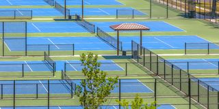 Weergeven van zij aan zij tennisbanen op een zonnige dag stock foto's