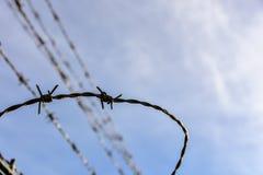 Weerhaakdraad tegen een blauwe hemel Stock Afbeelding