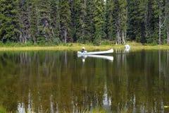 Weerspiegel Meer en een witte kanovisser. Royalty-vrije Stock Foto's