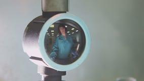 Weerspiegeld in rond instrument giet de laboratoriummedewerker vloeistof van buis aan bol stock video