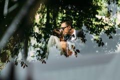 Weerspiegeling van de kus van het mooie paar naast de auto Stock Foto's