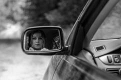 Weerspiegeling van een meisjeszitting in de auto in een autospiegel Stock Afbeeldingen