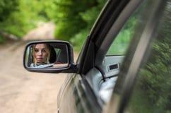 Weerspiegeling van een meisjeszitting in de auto in een autospiegel Stock Foto