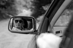 Weerspiegeling van een meisjeszitting in de auto in een autospiegel Royalty-vrije Stock Foto