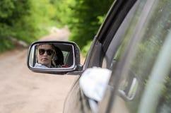 Weerspiegeling van een meisjeszitting in de auto in een autospiegel Stock Foto's