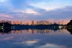 Weerspiegeling van het inbouwen van het meer bij zonsopgang bij oever van het meer Singa Stock Foto's