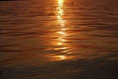 Weerspiegeling van zonlicht tijdens zonsondergang in schoon water royalty-vrije stock afbeeldingen