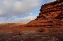 Weerspiegeling van zonsondergang op klippen stock foto's