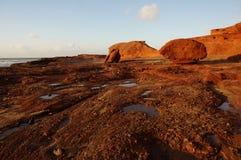 Weerspiegeling van zonsondergang op klippen stock afbeelding