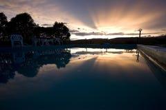 Weerspiegeling van zonsondergang over zwembad Stock Afbeeldingen